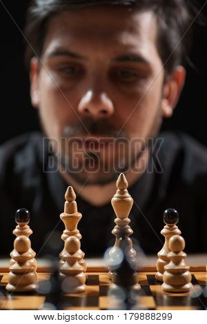 Portrait of adult man who is participating in chess game. Focus on chess figures.