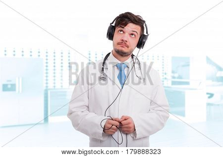 Male Doctor With Headphones Listening Music