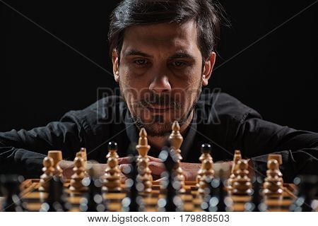 Portrait of adult man who is participating in chess game. Focus on man.