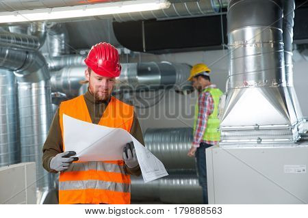 Workers making final touches to HVAC system. HVAC system stands for heating ventilation and air conditioning technology. Team work HVAC indoor environmental comfort concept photo.