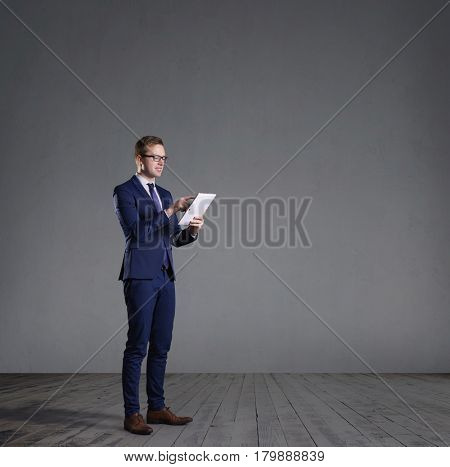 Businessman with computer tablet standing in front of a grey wall. Business, office, concept.