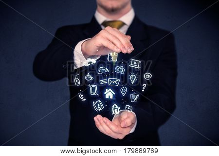 Blue multimedia icons in the hands of a businessman