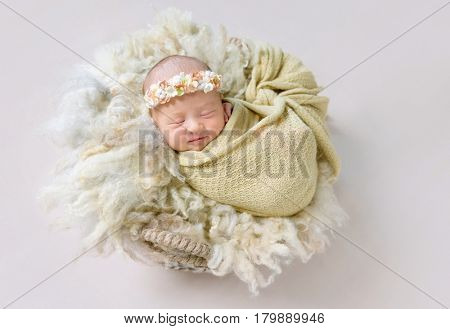Lovely smile of a tiny little girl sleeping, wrapped up with a warm blanket