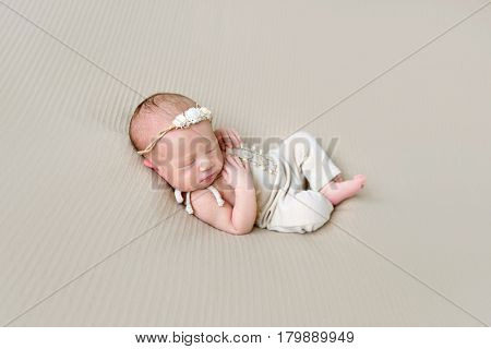 Sweet dreams of a baby girl in a hairband and lovely costume sleeping her side