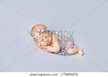 Naked baby girl wearing flowery hairband sleeping on her side, hands pressed to the cheek