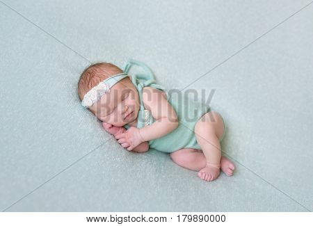 Aborable baby napping oh her side, wearing greenish dress and a flowery hairband