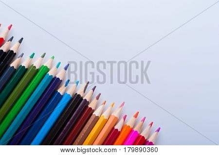 Stationary supplies. Group of sharpened bright pencils on white. Multicolored crayons background with copyspace. Drawing and sketching tools.