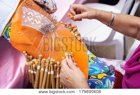 Detailed view of an elderly woman hands working with bobbin lace