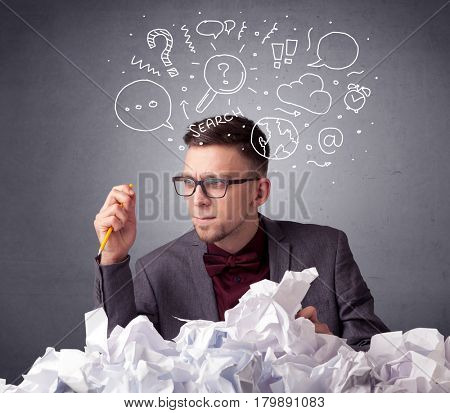 Young businessman sitting behind crumpled paper with mixed doodles over his head