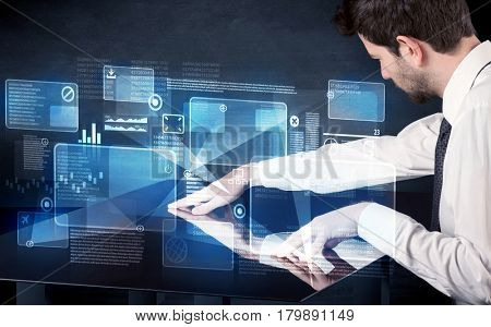 Man pressing technology smart table interface with blue graphs