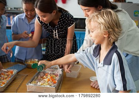 Bangkok , Thailand - November 23, 2012:  In a elementary school in Bangkok, young schoolchildren take a cooking class. Food is important in Thailand, it is part of the culture.