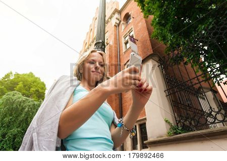 Young beautiful woman standing with mobile phone against the background of old brick building. Building of the Collegium Mayus. Jagiellonian University in Krakow. Student life