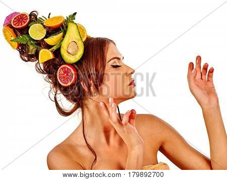 Hair mask from fresh fruits on woman head. Portrait in profile of girl with beautiful face and hairstyle in spring flowers girl touches smooth skin with finger as symbol lifestyle on isolated.