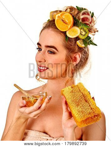 Honey facial mask with fresh fruits for hair and skin on woman head. Girl with beautiful face hold honeycombs for homemade organic skin and hair therapy. Concept of healthy and beauty hair and skin.