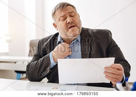 Serious complaints. Diligent distressed corpulent gentleman reading a recent sales report and being concerned about the future while fixing his tie