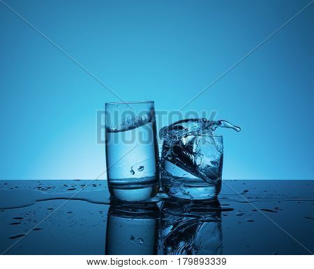 Сreative splashing water in the glass on blue background.
