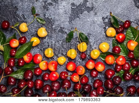 Fresh ripe cherry with green leaves on dark background. Top view, copy space