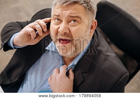 Would you hold a second. Burned out hard working chubby man talking on the phone with someone telling them he not feeling well