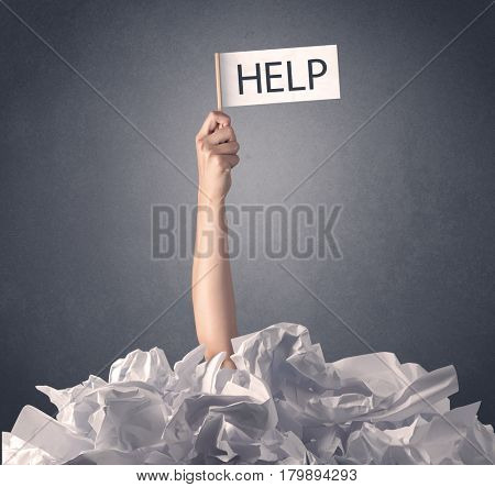 Female hand emerging from crumpled paper pile holding help sign