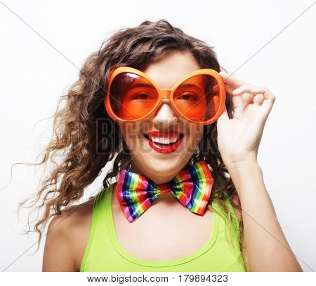 Playful young curly woman with party glasses.