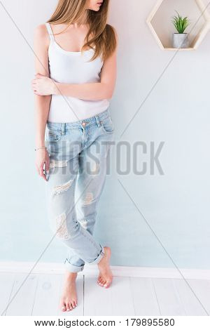Young girl with long brown hair in blue jeans and white singlet. Fashion girl posing in jeans in the studio. Sexy woman wearing denim with holes. Street style fashion girl.