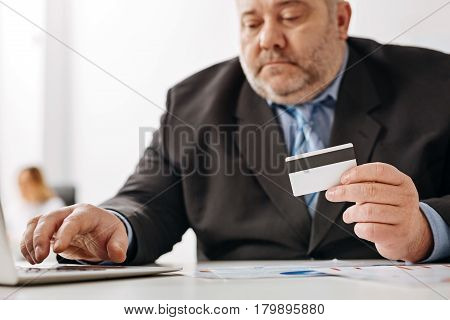 Using technology. Engaged attentive weary man holding his credit card and entering its number while using a laptop
