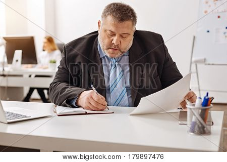 Thorough analysis. Diligent scrupulous puffy man fulfilling his work while analyzing a report and making some notes