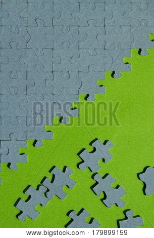 jigsaw puzzle pieces on green background with copy space vertical view