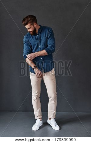Used to look perfect. Full length of handsome young man adjusting his sleeve while standing against grey background