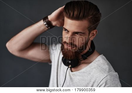 Calm and confident. Handsome young man wearing headphones around his neck and running his hand through his hair while standing against grey background