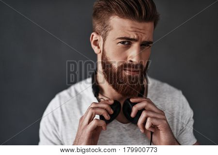 Feeling suspicious. Handsome young man wearing headphones around his neck and making a face while standing against grey background