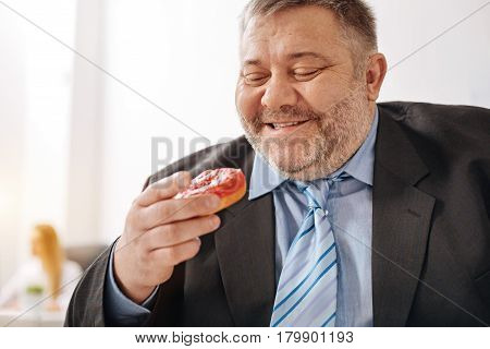 Uncontrollable desires. Excessive overweight hungry man holding a doughnut in his hand and enjoying the thought of eating it while sitting at his workplace