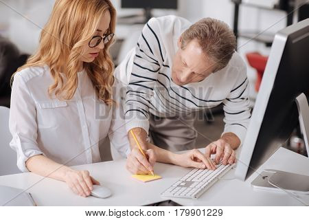 Always ready to help newcomer. Skilled friendly proficient office manager standing in the office and helping newcomer while working on the project and taking notes