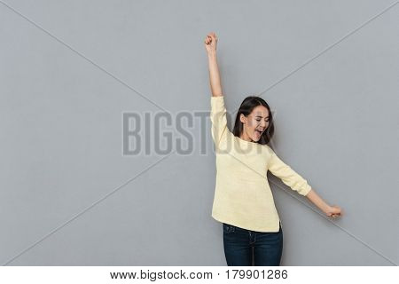 Cheerful excited young woman with raised hands standing and shouting over grey background