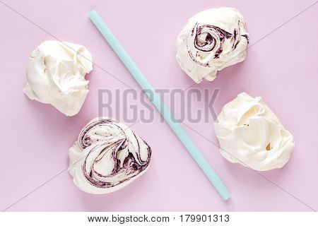 Meringues and drinking straws on pink background. Minimal food photography still life