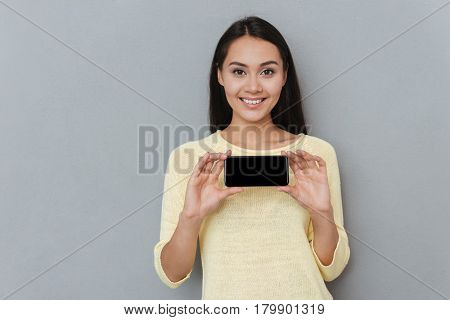 Cheerful attractive young woman holding blank screen cell phone over grey background