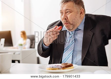 Too many sweets. Outsized compulsive unhealthy man sitting at his workplace and stuffing himself with baked sweets while looking rather unhealthy