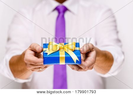 Male hands holding a gift box. Present wrapped with ribbon and bow. Christmas or birthday blue package. Man in white shirt and necktie.