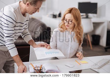 All thoughts about you. Charismatic skilled mature businessman standing in the office and working on the project while flirting and touching young colleagues hand