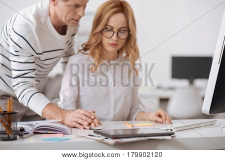 Falling in love with you. Insistent flirting aging businessman standing in the office and working on the project while flirting and touching young secretary hand