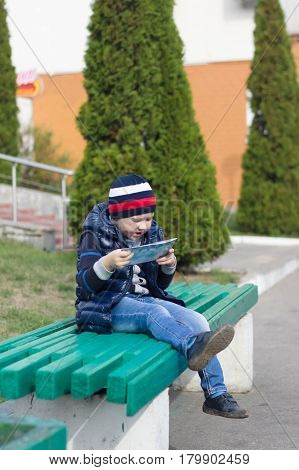the little boy took seat on a bench in park and reads the book