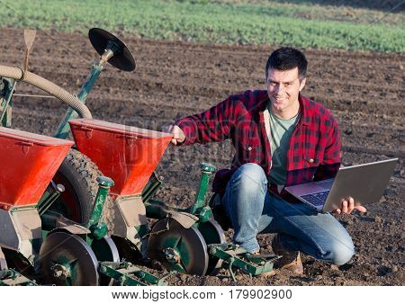 Farmer With Laptop And Sowing Equipment