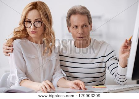 Sexual harassment in business office. Cheerful flirting mature businessman sitting in the office and working on the project while flirting and touching young secretary shoulder
