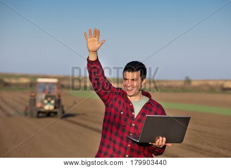 Satisfied Farmer With Laptop And Tractor