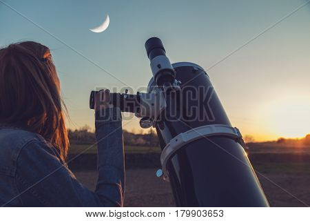 Girl looking at the Moon through a telescope.
