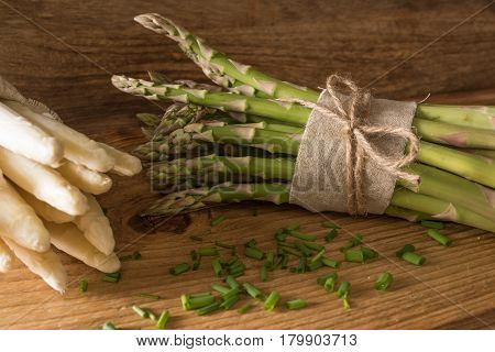 Bound green and white asparagus with chives on rustic wood