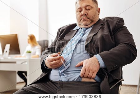 Consequents of excessiveness. Stout sad compulsive guy suffering from his excess weight causing him a lot of trouble and preparing doing an injection