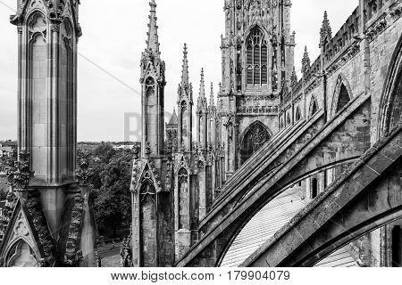York Minster is a cathedral in York one of the leading examples of english gothic architecture. Tower and flying buttresses on the roof of York Minster in black and white. York North Yorkshire United Kingdom