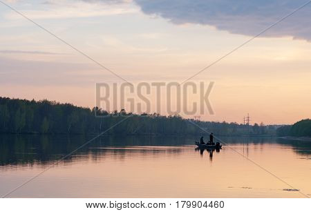 Two fisherman on boat fishing at sunset at Moscow region