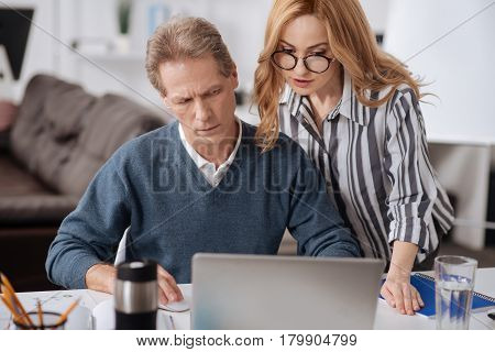 Showing the temptation. Beautiful young involved businesswoman standing in the office next to the coworker while using laptop and seducing the man